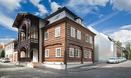 Skleněný dům mezi roubenkami
